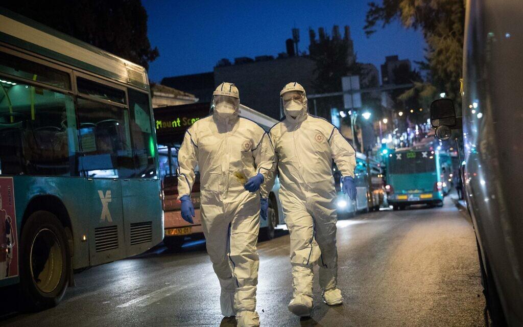 Des secouristes du Magen David Adom portant une tenue de protection contre le nouveau coronavirus arrivent pour tester un patient présentant des symptômes de Covid-19, à Jérusalem, le 16 mars 2020. (Crédit : Yonatan Sindel/Flash90)