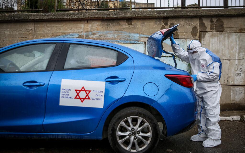 Un travailleur de Magen David Adom portant des vêtements de protection contre le coronavirus arrive pour tester un patient présentant des symptômes de COVID-19 (coronavirus), à Jérusalem, le 16 mars 2020. (Crédit : David Sindell/Flash90)