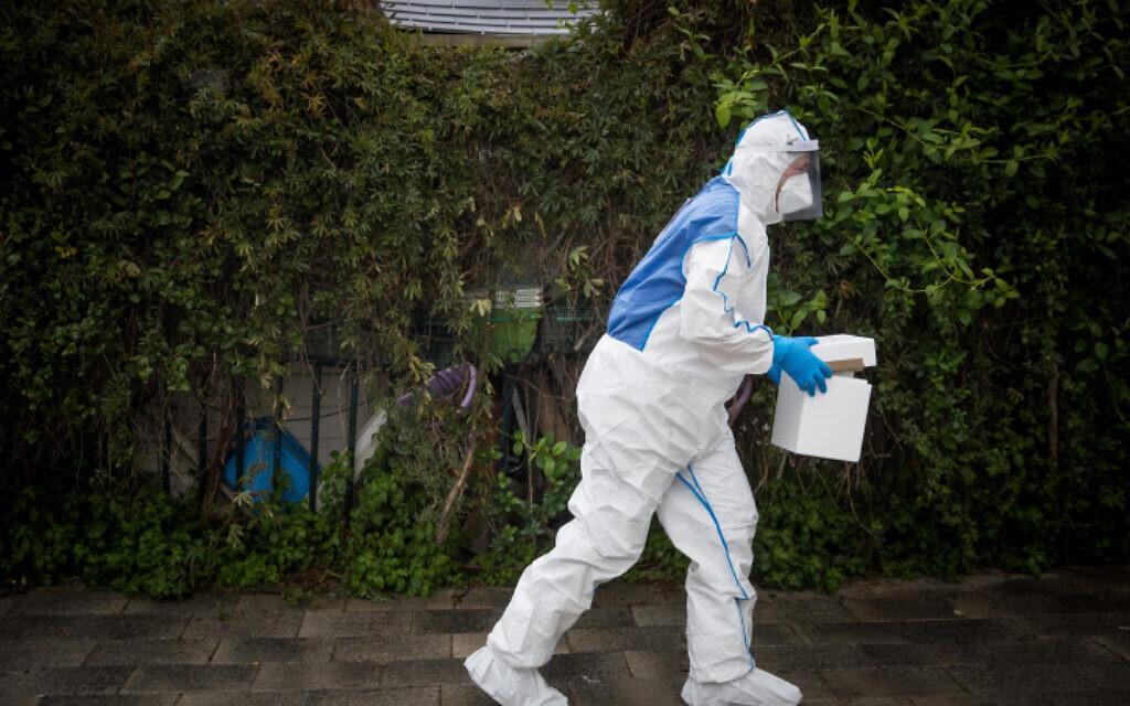 Un secouriste du Magen David Adom portant une tenue de protection contre le coronavirus arrive pour tester un patient présentant des symptômes de Covid-19, à Jérusalem, le 16 mars 2020. (Crédit : Yonatan Sindel/Flash90)