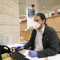 Un employé de banque muni d'un masque de protection contre le coronavirus, à Jérusalem, le 17 mars 2020. (Crédit : Yossef Zamir/Flash90)