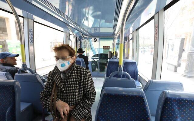 Des Israéliens munis de masques de protection, dans un bus à Jérusalem, le 17 mars 2020. (Crédit :Yossi Zamir/Flash90)