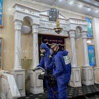 Des agents portant des vêtements de protection désinfectent une synagogue à Bat Yam, le 18 mars 2020, dans le cadre des mesures visant à prévenir la propagation du coronavirus. (Flash90)