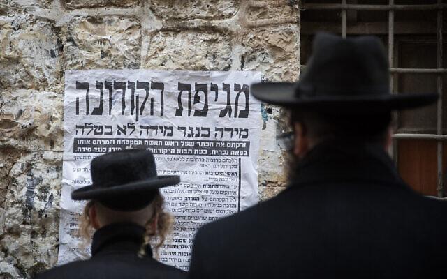 """Des hommes ultra-orthodoxes regardent un """"pashkevil"""", une affiche informative sur le coronavirus, dans le quartier de Mea Shearim à Jérusalem, le 18 mars 2020. (Crédit : Yonatan Sindel/Flash90 )"""