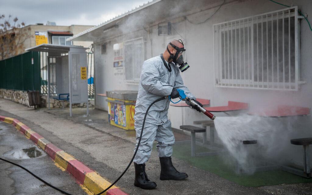 Un pompier israélien portant une tenue de protection désinfecte une gare routière dans la ville ultra-orthodoxe de Kiryat Ye'arim (Telz-Stone), le 18 mars 2020, après que dix-sept habitants de la ville ont été diagnostiqués porteurs du coronavirus. (Crédit : Yonatan Sindel / Flash90)