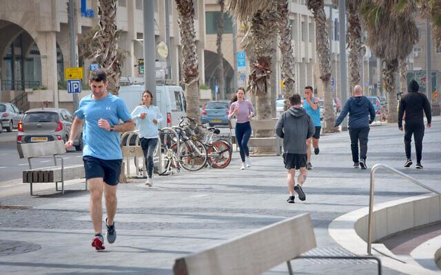 Des gens courent près de la plage à Tel-Aviv le 19 mars 2020 (Crédit : Avshalom Sassoni/Flash90)