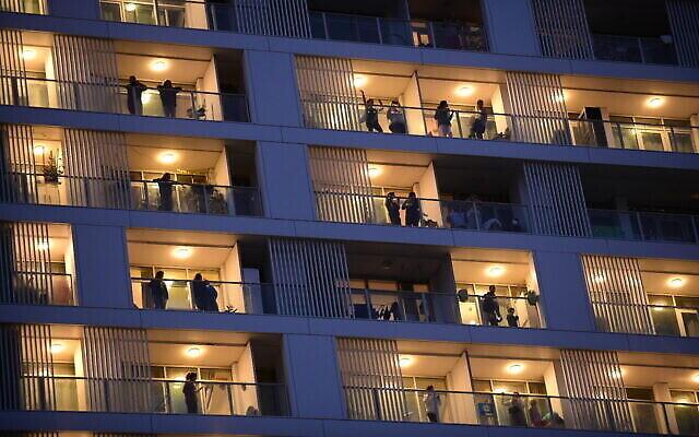 Les habitants de Tel Aviv sur leurs balcons, applaudissent les soignants mobilisés pour la lutte contre le coronavirus, le 19 mars 2020. (Crédit : Tomer Neuberg/Flash90)