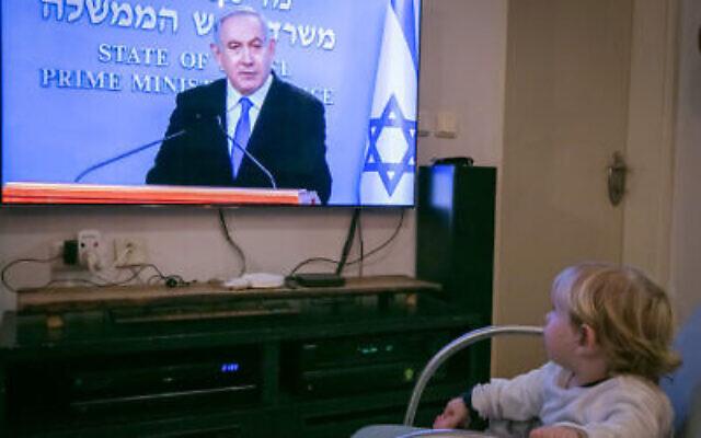 Un enfant regarde le Premier ministre Benjamin Netanyahu pendant une conférence de presse en direct sur les nouvelles restrictions gouvernementales pour la population concernant le coronavirus, le 19 mars 2020. (Chen Leopold/Flash90)
