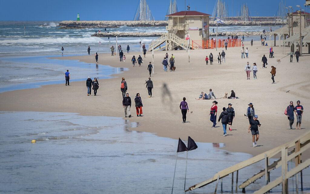 Des Israéliens sur la plage de Tel-Aviv malgré les ordres du gouvernement d'éviter les rassemblements publics en raison de la propagation du nouveau coronavirus, le 21 mars 2020. (Crédit : Avshalom Sassoni/Flash90)