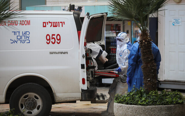 Des ambulanciers portent un équipement de protection en mesure préventive contre le coronavirus alors qu'ils évacuent une femme qui pourrait avoir attrapé le COVID-19 à l'hôpital Hadassah Ein Kerem de Jérusalem, le 22 mars 2020 (Crédit : Flash90)