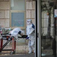 Des travailleurs du Magen David Adom portant des vêtements de protection, comme mesure préventive contre le coronavirus évacuant une femme à l'hôpital Hadassah Ein Karem, à Jérusalem, le 22 mars 2020. (Crédit : Flash90)