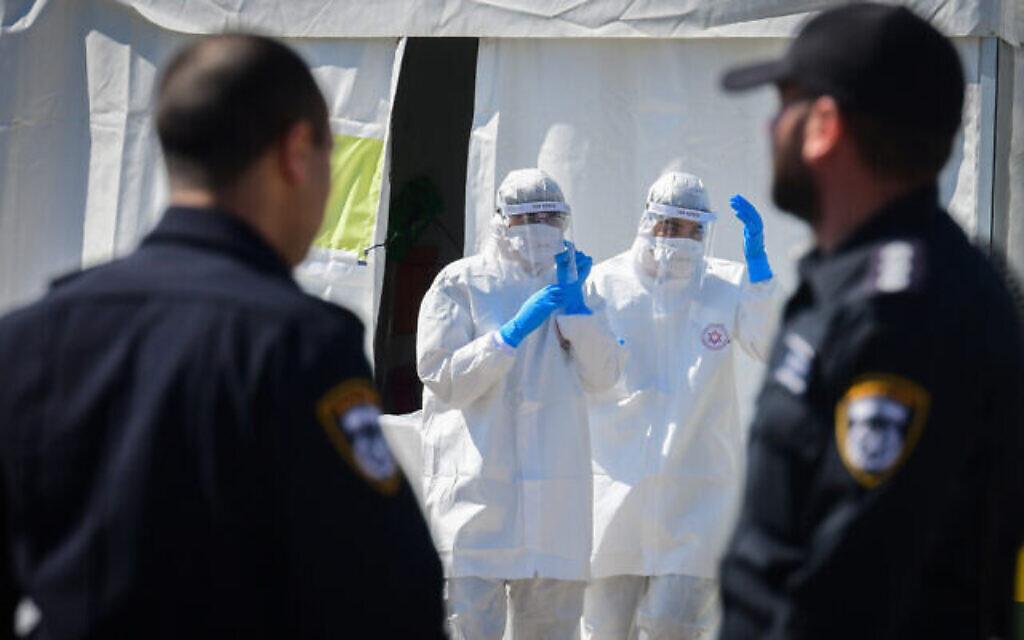 Des membres de l'équipe médicale du Magen David Adom, portant des équipements de protection, manipulent un échantillon de coronavirus sur un site de drive-in pour le tester à Tel Aviv, le 22 mars 2020. (Flash90)