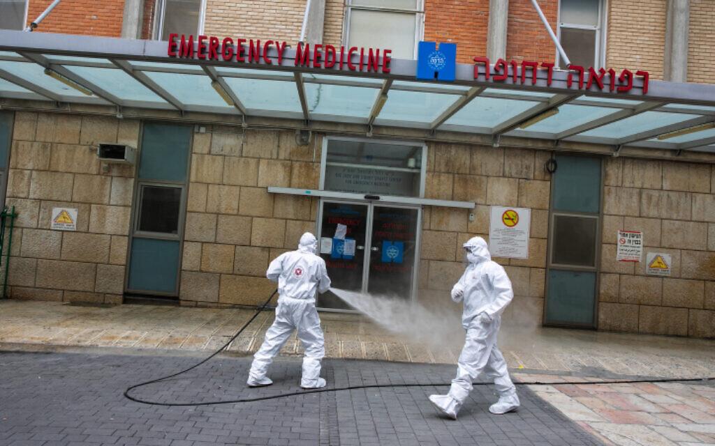 Un pompier israélien portant une tenue de protection désinfecte l'entrée des urgences de l'hôpital Hadassah Ein Karem à Jérusalem, le 22 mars 2020. (Crédit : Olivier Fitoussi/Flash90)