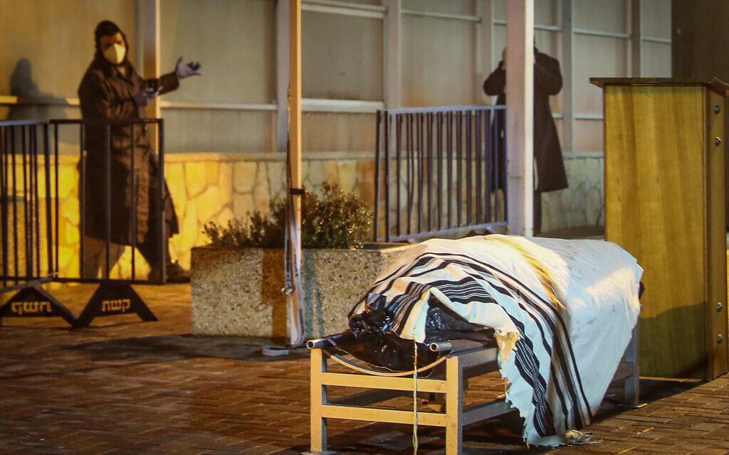 Un homme se tient aux côtés de la dépouille du survivant de la Shoah Aryeh Even, 88 ans, première victime de la pandémie de coronavirus en Israël, au cimetière Har HaMenuchot de Jérusalem, le 22 mars 2020 (Crédit : Yonatan Sindel/Flash90)
