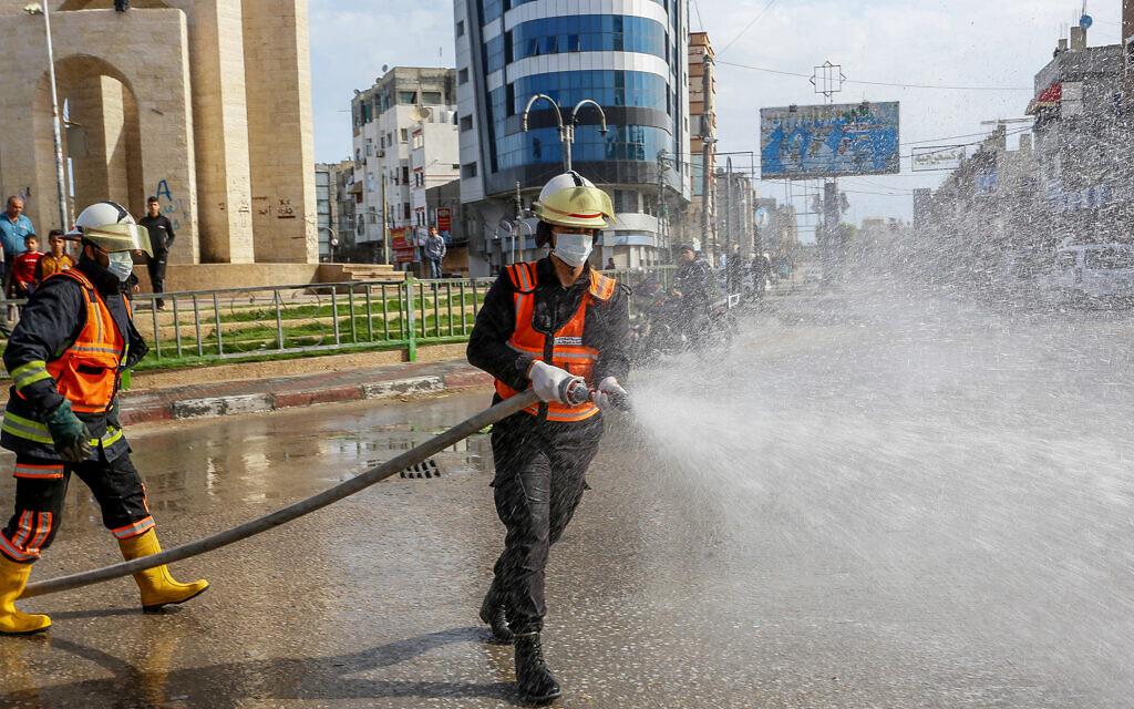Des agents de la défense civile palestinienne désinfectent une rue à Rafah, dans le sud de la bande de Gaza, le 23 mars 2020, après que les deux premiers cas de coronavirus à Gaza ont été confirmés. (Crédit : Abed Rahim Khatib/Flash90)