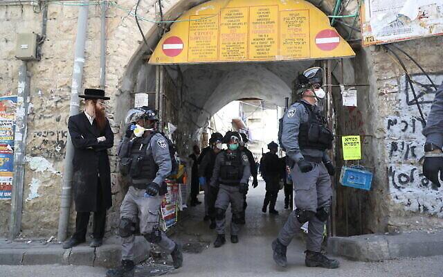 Des policiers dans le quartier juif ultra-orthodoxe de Mea Shearim à Jérusalem ferment des magasins et dispersent des rassemblements publics sur ordre du gouvernement afin de contenir la propagation du coronavirus, le 24 mars 2020. (Yonatan Sindel/Flash90)