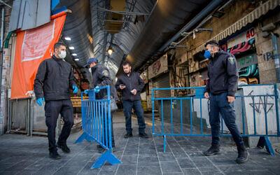 Des employés de la municipalité de Jérusalem ferment les entrées du marché  Mahane Yehuda à Jérusalem, le 24 mars 2020 (Crédit : Yonatan Sindel/Flash90)