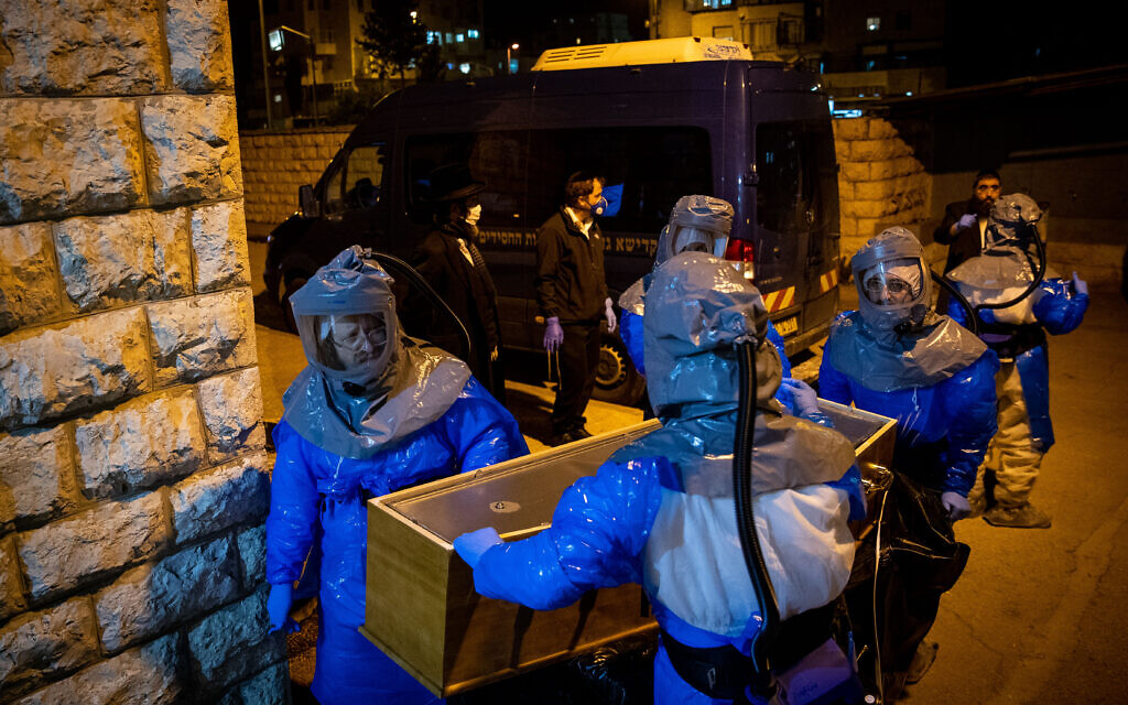 Chevra Kadisha workers wearing protective clothes, carry the body of a man died from complications of Coronavirus (COVID-19) infection, at the Shamgar Funeral Home in Jerusalem on March 24, 2020. Photo by Yonatan Sindel/Flash90 *** Local Caption *** קורונה וירוס חברה קדישא ירושלים לבושים בגדים מגן נגד