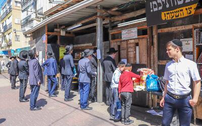 Des juifs ultra-orthodoxes prient à l'extérieur d'une synagogue à Bnei Brak, le 25 mars 2020. (Yossi Aloni/Flash90)