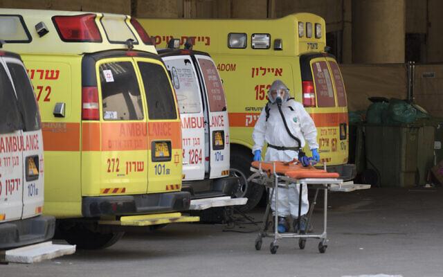 Photo d'illustration : Un membre d'une équipe médicale nettoie et désinfecte une ambulance à l'hôtel Dan Panorama, à Tel Aviv, qui a été transformé en structure de quarantaine dans le cadre de l'épidémie de coronavirus, le 26 mars 2020. (Crédit : Gili Yaari / Flash90)