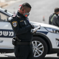 Un agent de la police des frontières muni de protections verbalise ceux qui enfreignent le confinement, à Jérusalem, le 26 mars 2020. (Crédit : Olivier Fitoussi/Flash90)