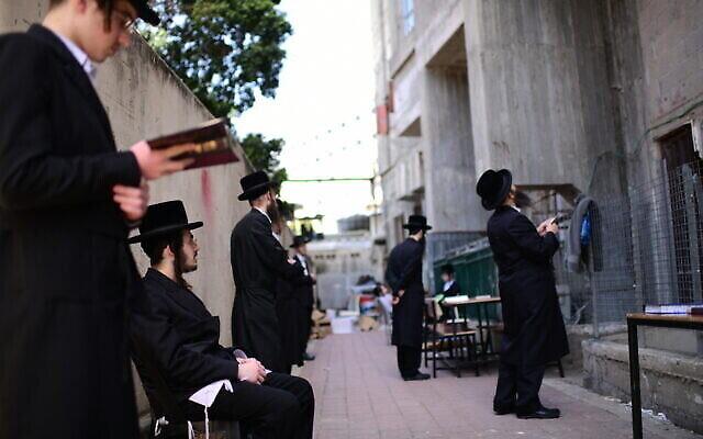 Des Juifs ultra-orthodoxes prient aux abords d'une yeshiva fermée dans la ville de Bnei Brak, le 26 mars 2020 (Crédit : Tomer Neuberg/Flash90)