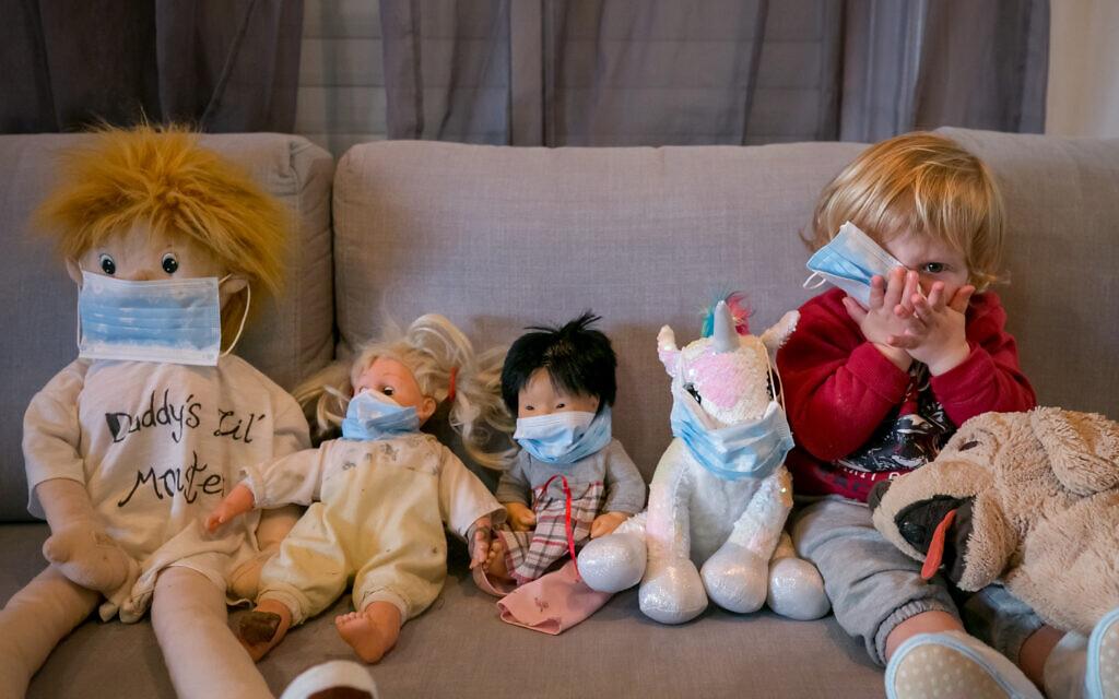 Des enfants, confinés à cause du coronavirus, jouent à mettre des masques sur leurs animaux en peluche, le 29 mars 2020. (Crédit : Chen Leopold/Flash90)
