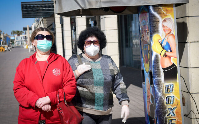 Deux femmes portent un masque le long de la promenade d'Ashkelon, en bord de mer, le 29 mars 2020 (Crédit : Flash90)