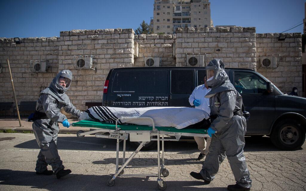 Illustration : Des employés de pompes funèbres portant des vêtements de protection transportent le corps d'un patient décédé du coronavirus (COVID-19), au Shamgar Funeral Home à Jérusalem, le 29 mars 2020. (Yonatan Sindel/Flash90)