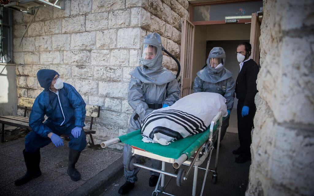 Des employés de la Chevra Kadisha portant des vêtements de protection, portent le corps d'un homme décédé des suites de complications d'une infection au Coronavirus (COVID-19), au salon funéraire Shamgar à Jérusalem, le 29 mars 2020. (Crédit : Yonatan Sindel/Flash90)