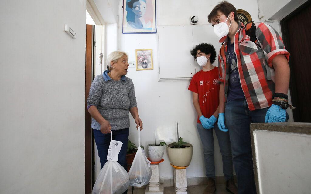 De jeunes bénévoles distribuent des repas chauds à des personnes âgées qui n'ont pas pu quitter leur domicile à cause du coronavirus, à Jérusalem, le 29 mars 2020. (Crédit : Yossi Zamir/Flash90)