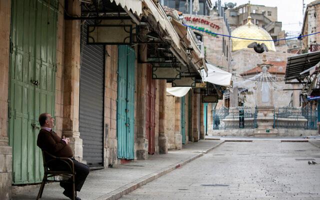 Un propriétaire de restaurant devant des magasins fermés dans la Vieille Ville de Jérusalem, le 30 mars 2020 (Crédit :  Olivier Fitoussi/Flash90)