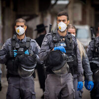 Des agents de police ferment des synagogues et dispersent des rassemblements publics dans le quartier juif orthodoxe de Mea Sharim à Jérusalem, le 31 mars 2020 (Crédit : Yonatan Sindel/Flash90)