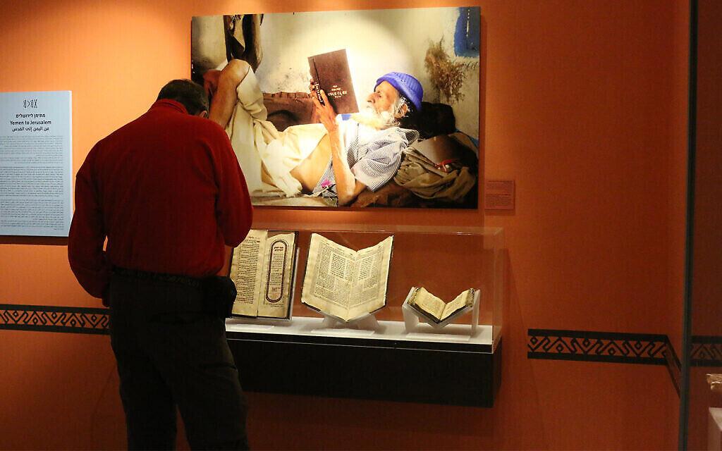 Un visiteur au Musée des pays de la Bible devant une photo de Naftali Hilger représentant un vieux Yéménite lisant un livre à l'envers. (Shmuel Bar-Am)