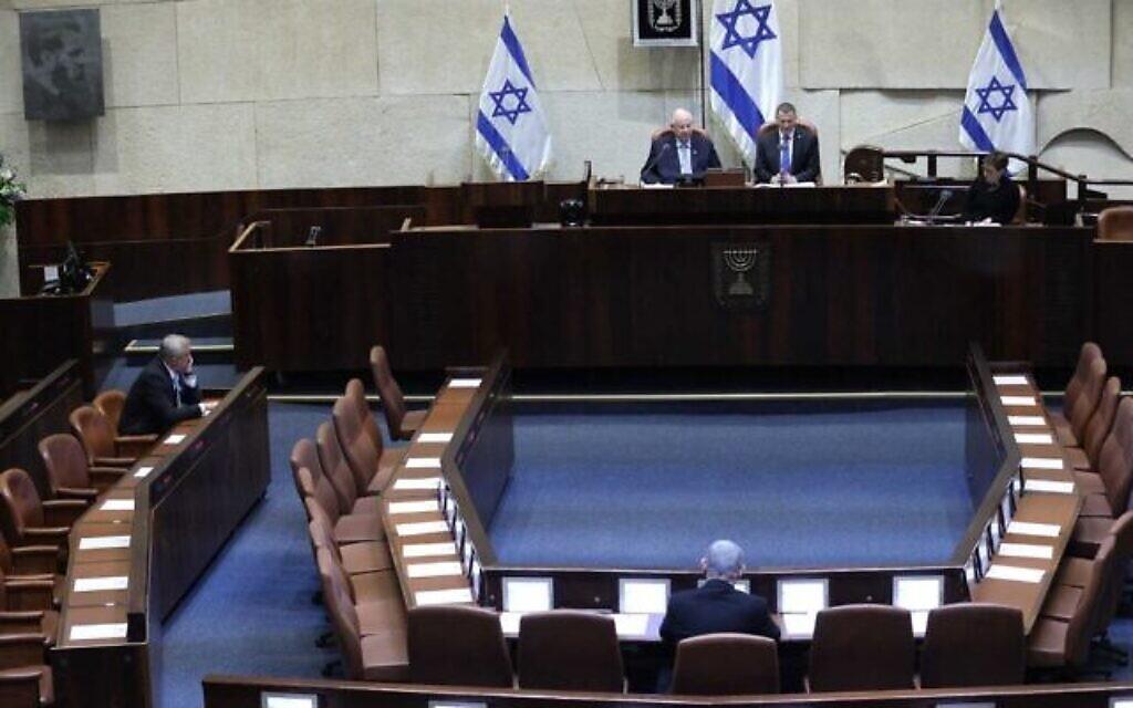 Un plénum presque vide, en raison des restrictions contre le coronavirus, lors de la prestation de serment de la 23e Knesset, le 16 mars 2020. À gauche, Benny Gantz. Au centre, de dos, Benjamin Netanyahu. (Gideon Sharon/ Porte-parole de la Knesset)