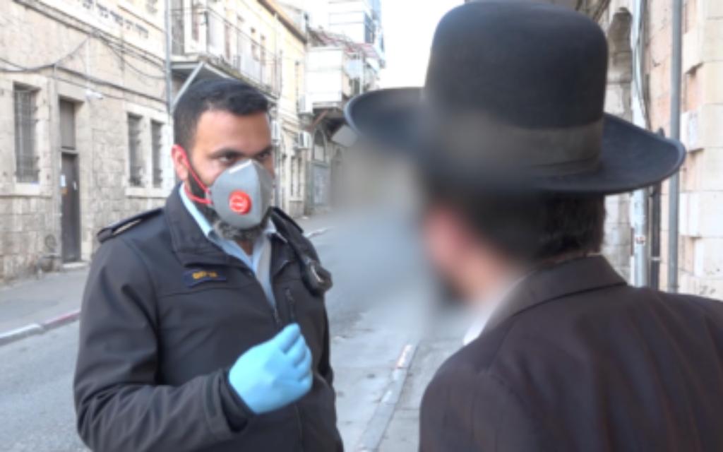 Un policier israélien donne une amende pour violation des restrictions anti-coronavirus gouvernementales dans le quartier Mea Sharim de Jérusalem, le 30 mars 2020 (Crédit : Police israélienne)