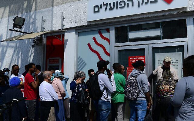 Des Israéliens font la queue devant une banque près du marché Hatikva, Tel Aviv, le 15 mars 2020. (Crédit : Tomer Neuberg/Flash90)