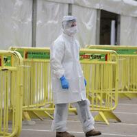Un employé de l'équipe médicale du Magen David Adom à un site de testage de coronavirus de type drive-in à Tel Aviv, le 20 mars 2020 (Crédit : Gili Yaari/Flash90)