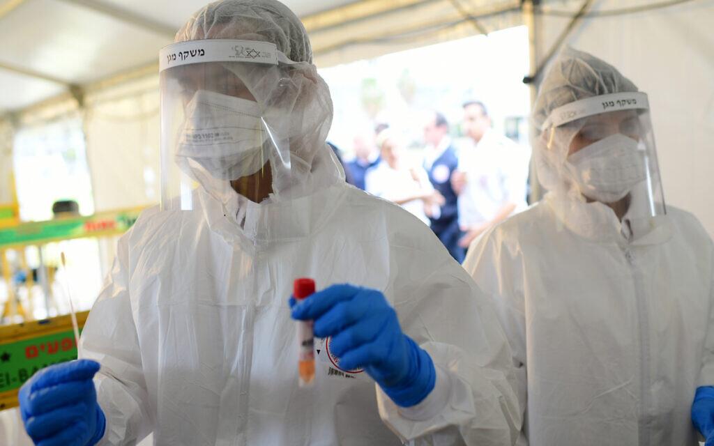 Des employés du Magen David Adom sur un site de drive-in collectent des échantillons pour des tests au coronavirus, à Tel Aviv, le 20 mars 2020 (Crédit : Tomer Neuberg/Flash90)
