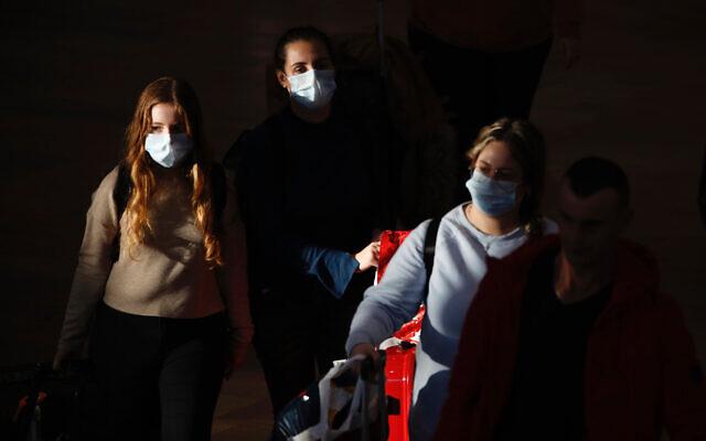 Des voyageurs portant des masques de protection arrivent à l'aéroport international Ben Gurion, près de Tel-Aviv, le 27 février 2020. (Crédit : AP/Ariel Schalit)