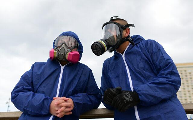 Des travailleurs portant des vêtements de protection désinfectent un terrain de jeu public à Bat Yam dans le cadre des mesures visant à prévenir la propagation du coronavirus, le 18 mars 2020. (Crédit : Tomer Neuberg/Flash90)
