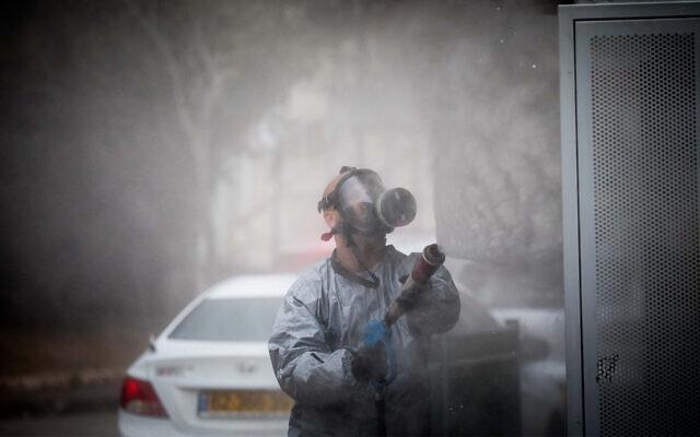 Un pompier israélien portant une tenue de protection désinfecte une station de bus dans la ville ultra-orthodoxe de Kyriat Ye'arim (Telz-Stone), le 18 mars 2020, après que dix-sept des habitants de la ville ont été diagnostiqués porteurs du coronavirus. (Crédit : Yonatan Sindel/Flash90)