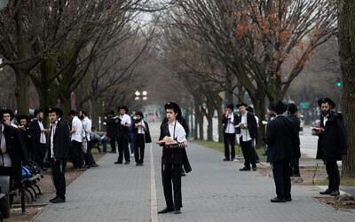 """Des hommes juifs respectent la """"distanciation sociale"""" alors qu'ils prient devant le siège mondial du mouvement Habad Loubavitch à Brooklyn, New York, le 20 mars 2020. (AP/Mark Lennihan)"""