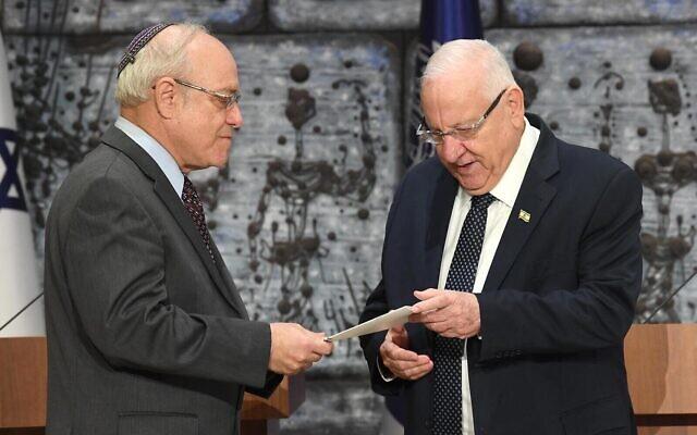 Le président de la commission centrale électorale, le juge de la Cour suprême Neal Hendel, (à gauche), remet les résultats officiels des élections à la 23e Knesset au président Reuven Rivlin, à la résidence du Président, le 11 mars 2020. (Mark Neyman/GPO)