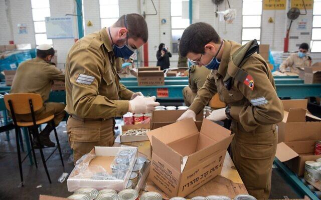 Les troupes israéliennes emballent des boîtes de nourriture dans le cadre des préparatifs de l'armée pour soutenir les lignes d'approvisionnement du pays face à  la pandémie de coronavirus en mars 2020. (Crédit : armée israélienne)
