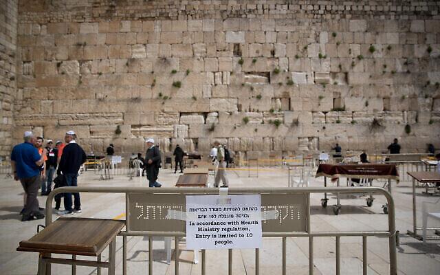 Illustration : les gens prient dans des espaces clos, ne permettant que 10 personnes à la fois, au Mur occidental, dans la Vieille Ville de Jérusalem, le 15 mars 2020. (Crédit : Yonatan Sindel / Flash90)