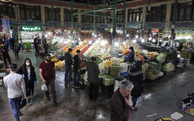 Des Iraniens, dont certains portent des masques de protection, devant des étales au Bazaar Tajrish dans la capitale de l'Iran de Téhéran, le 12 mars 2020. (AFP photo)