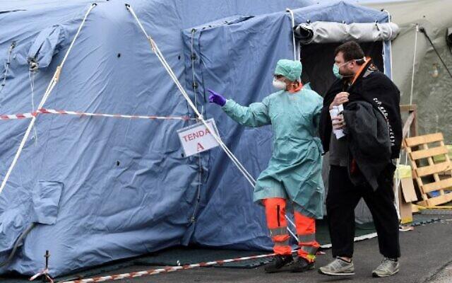 Un employé hospitalier portant un masque et un équipement de protection, accompagne un patient à l'unité de radiologie dans une structure temporaire d'urgence installée devant le service des urgences, où n'importe quel patient qui arrive en présentant les symptômes du coronavirus est testé, à l'hôpital de Brescia en Lombardie, le 13 mars 2020. (Miguel Medina/AFP)