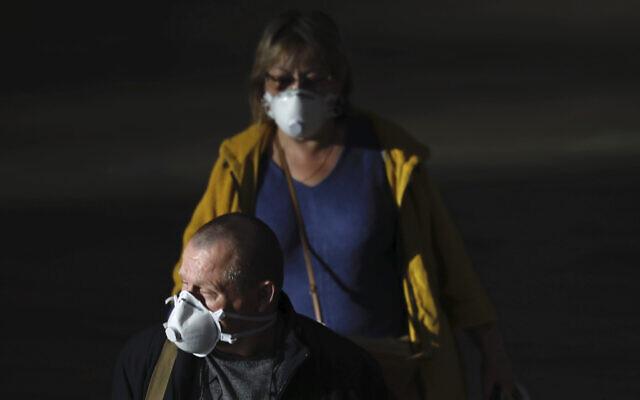 Des passagers portent des masques pour se protéger du coronavirus à l'aéroport Ben Gurion, à proximité de Tel Aviv, en Israël, le dimanche 8 mars 2020. (AP Photo/Ariel Schalit)