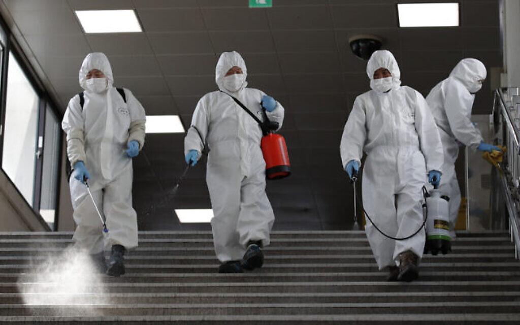 Des employés portant des masques de protection désinfectent par précaution contre le nouveau coronavirus dans une station du métro de Séoul, en Corée du Sud, le vendredi 13 mars 2020. (AP Photo/Lee Jin-man)