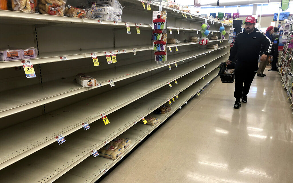 Un client passe devant les étagères vides où le pain est normalement proposé à la vente dans un supermarché, le dimanche 15 mars 2020 à Boston. (AP Photo/Steven Senne)